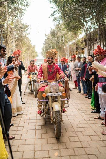 Groom entering his wedding on a bike