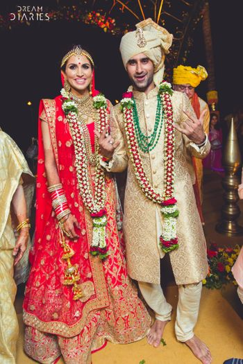Red bridal lehenga with beige groom sherwani