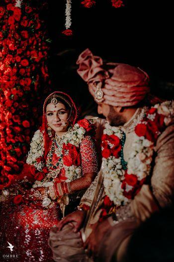 couple phera shot wearing red and white jaimalas