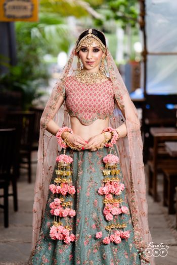 A beautiful bride in a stunning outfit and off-beat floral kaleere and gold jewellery.
