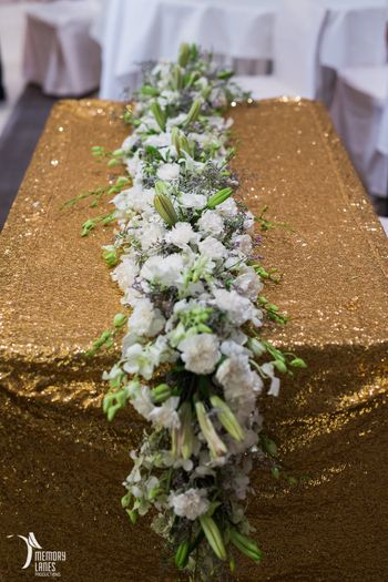 Photo of Gold Glitter Table with Floral Runner Decor