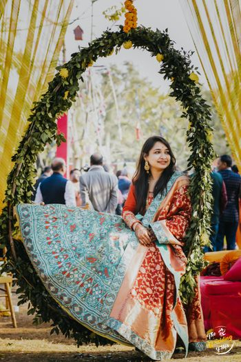 A to be bride sitting in a floral wreath at her mehndi