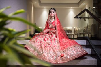 bride sitting on stairs showing off bright red lehenga