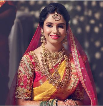 A south Indian bride in a yellow and red kanjeevaram and gold temple jewellery