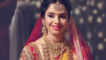 Photo of A south Indian bride in a yellow and red kanjeevaram and gold temple jewellery