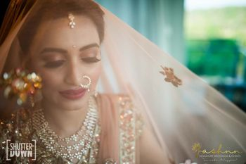 bridal portrait with a veil out of peach dupatta