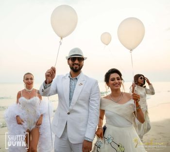Photo of couple entering holding balloons for beach wedding
