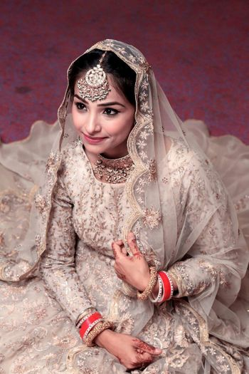 A bride in a silver bridal lehenga and an oversized mangtikka