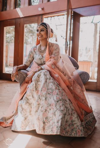 A bride in a white lehenga with floral embroidery with a peach dupatta
