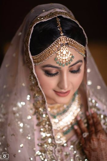 contrasting green jewellery with light pink lehenga for bride