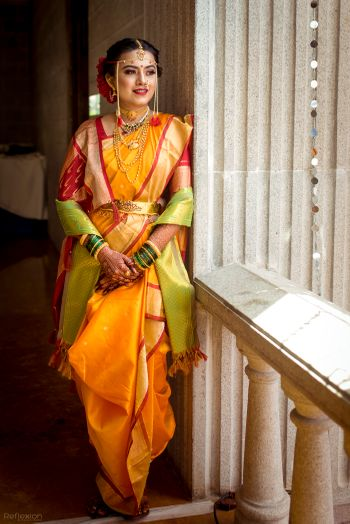 A Marathi bride in a yellow saree with red border