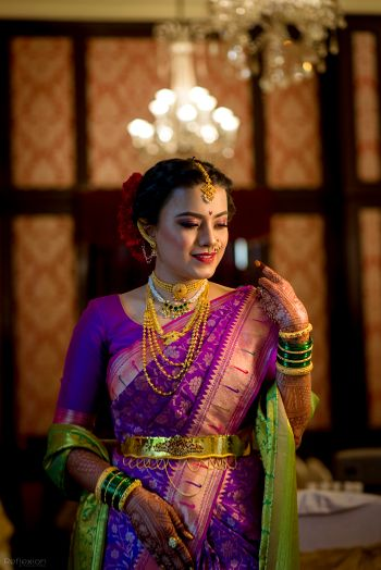Photo of A Marathi bride in a purple saree with gold jewellery