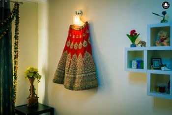 Photo of Red and Gold Bridal Lehenga on a Hanger Shot