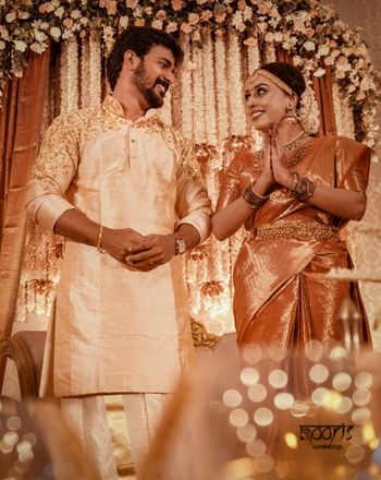 A south Indian couple in coordinated gold and creme outfits