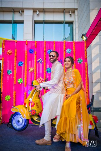 A bride and groom in coordinated outfits on their mehendi, posing with fun props