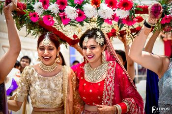 Photo of A bride laughs under a phoolon ki chaadar with her sister