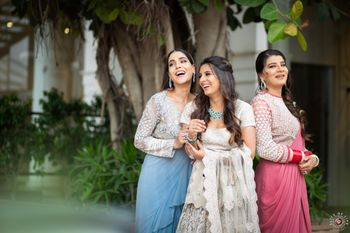 Photo of A bride-to-be laughing with her bridesmaids in coordinated pastel outfits