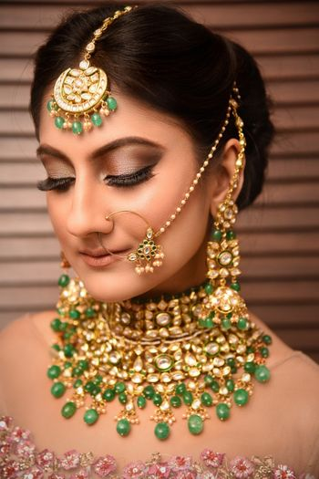 Closeup of a bride wearing a choker and a light nath with green beads