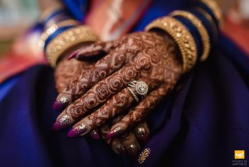 bridal hands with maroon manicure and engagement ring