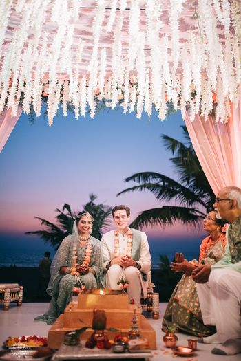 A couple sitting for their pheras in their white and pink mandap