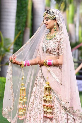 Bride in light pink lehenga with matching kaleere