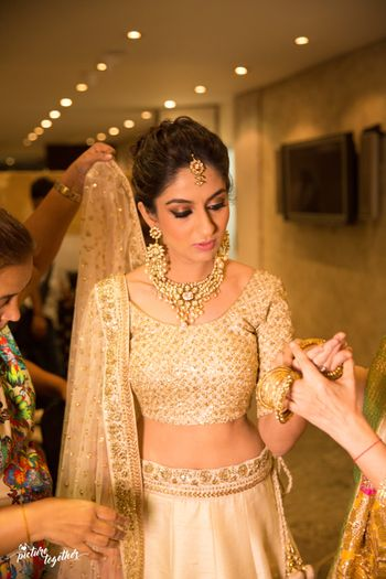 Photo of bridal shot in gold lehenga getting ready