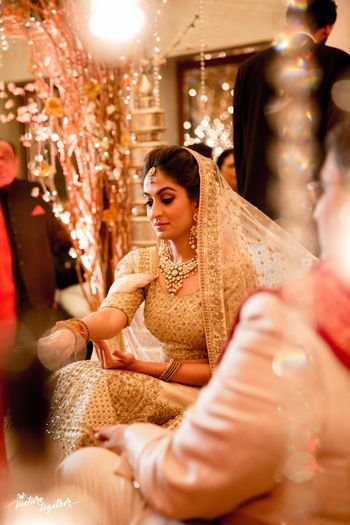 Photo of wedding day bridal portrait in a gold bridal lehenga