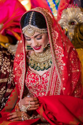 bride in red and gold lehenga with contrasting green jewellery