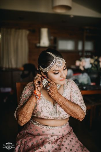A bride in a pink lehenga getting ready for her wedding