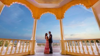 A couple pose at a palace balcony for their prewedding shoot