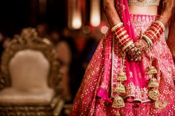 Bride in a heavy bright pink lehenga with chooda & gold kaleere.