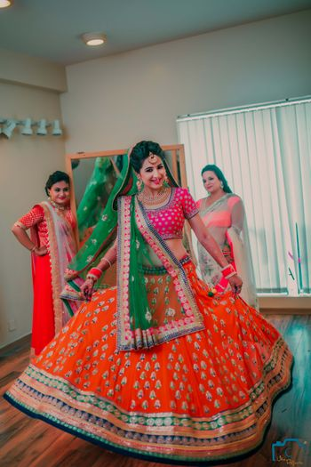 Photo of Twirling Bride in orange lehenga