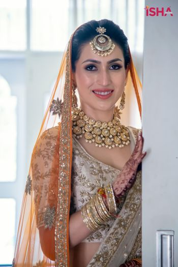 Photo of bride in an ivory and gold lehenga with orange second dupatta