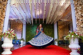 bride twirling in a royal blue lehenga