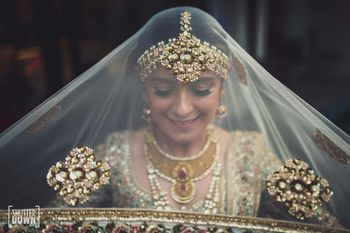 bride holding her sabysachi dupatta as veil shot