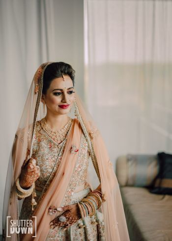 bride in light peach and mint lehenga