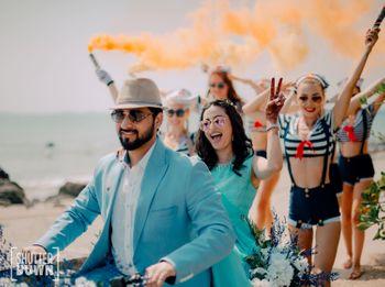 couple entry on bike with smoke sticks for beach wedding