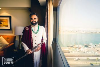 Photo of groom in white sherwani with stole and sword