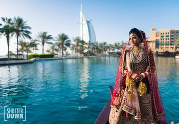 Photo of bridal portrait outdoors in maroon velvet lehenga