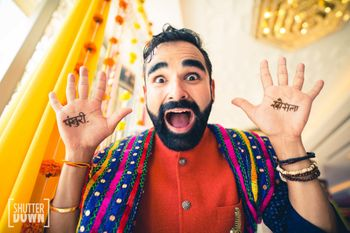 Photo of crazy groom showing off mehendi shot