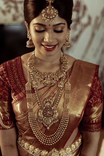 gold bridal look with layered temple necklaces