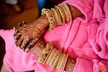 gold kade and mehendi on bridal hands