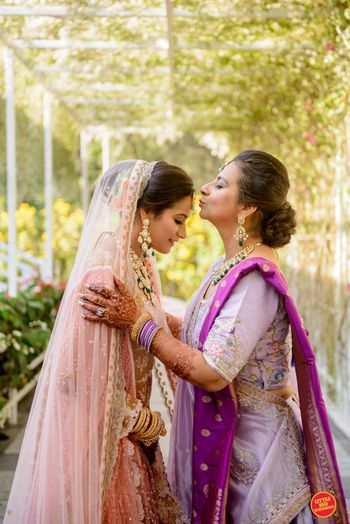 bride on her wedding day with mom kissing her forehead