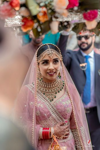 A bride in a light pink lehenga with gold and green jewellery