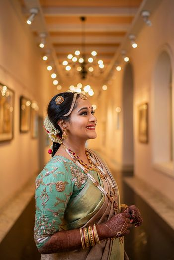 Photo of A south Indian bride with a unique, embroidered blouse on her wedding day