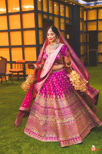 Photo of A bride twirling in her purplish-pink lehenga.