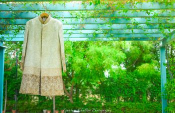 Cream Sherwani with Gold Border Work on a Hanger