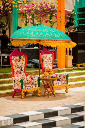 Printed wooden chairs with a standing umbrella for mehndi decor