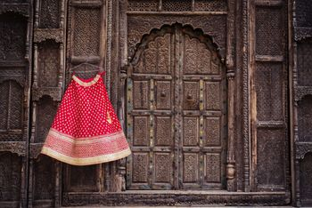 Photo of Red Bridal Lehenga with Border on a Hanger