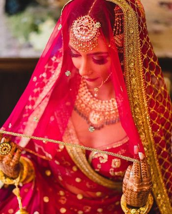 Photo of bride holding her sabyasachi dupatta as a veil